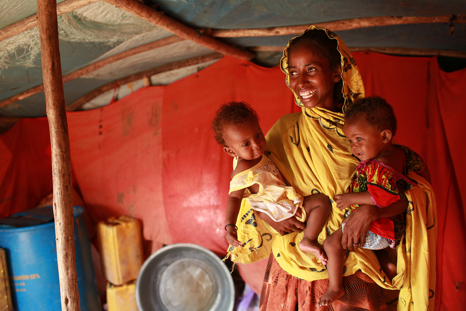 Photographing for UNICEF in Djibouti... 19 year old Maria Abdullahi, who looks after her own child, Nouria, and her cousin's child, Maysun, both 9 months old, living in a tent in a refugee camp in the desert in Djibouti, East Africa - they are refugees from Somalia. Maysun's own mother abandoned her, and Maria took her in, breastfeeding her along with her own daughter. She does the whole thing with such grace and humour, and so few resources. Total inspiration.