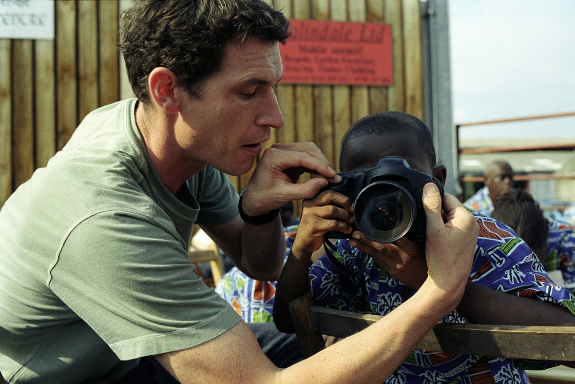 TIM HETHERINGTON SHOWING A BLIND CHILD FROM SIERRA LEONE HOW TO USE A CAMERA, AROUND 2004. IT'S FIVE YEARS TODAY SINCE HE WAS KILLED IN LIBYA, BUT HE INSPIRED AND KEEPS INSPIRING SO MANY YOUNG PHOTOGRAPHERS TO WORK MORE CREATIVELY. CAN'T CLAIM TO BE A YOUNG PHOTOGRAPHER ANY MORE, BUT WAY BACK HE GAVE ME GREAT ADVICE WHEN I WAS STUCK WITH ONE PROJECT: 'SHOW IT HOW IT FEELS, NOT HOW IT LOOKS.' I REMEMBER THOSE WORDS ON ALMOST EVERY SHOOT I DO.